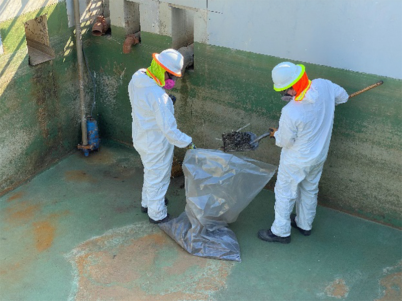 crew in hazmat suits dump debris into waste bags for disposal